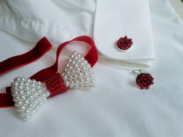 Biała perłowa mucha męska na czerwonym pasku, czerwone koralikowe spinki do mankietów